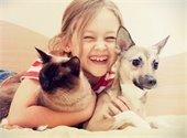 girl hugging dog and cat