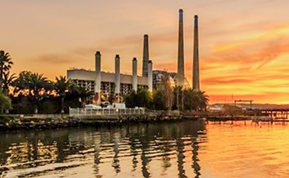 view of a industrial building at sunset on a bay